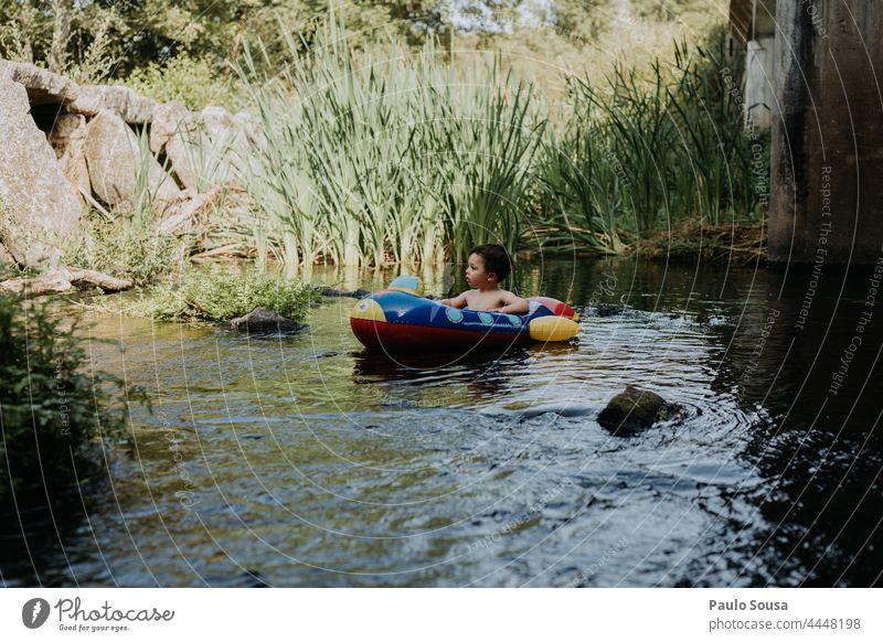 Kind auf Schlauchboot aufblasbar Boot Kindheit Sommer Fluss Wasser niedlich Freizeit Glück Urlaub Lächeln Feiertag im Freien jung heiter Lifestyle Kaukasier