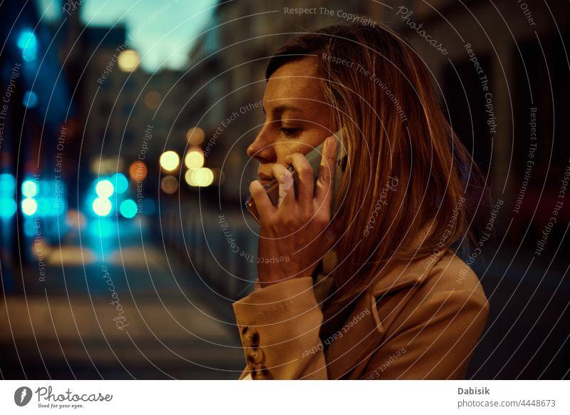 Frau benutzt Smartphone in nächtlicher Stadtstraße Telefon Großstadt Nacht Straße verwenden online Stadtleben urban Lifestyle Mobile Nachricht Internet