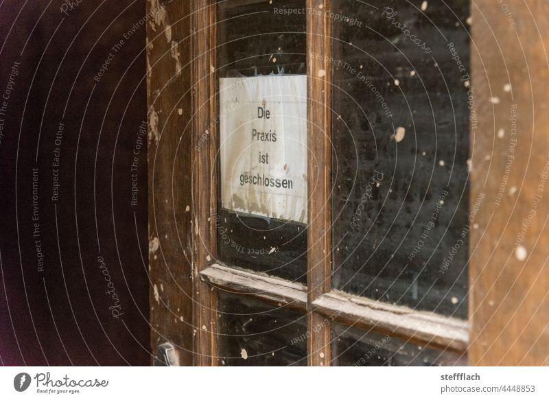 """Improvisiertes """"Praxis geschlossen"""" Schild in einem Fenster einer Holztür nach der Flut im Ahrtal Tag Hauseingang Tür Arzt Arztpraxis Staub Schlamm Flutwelle"""