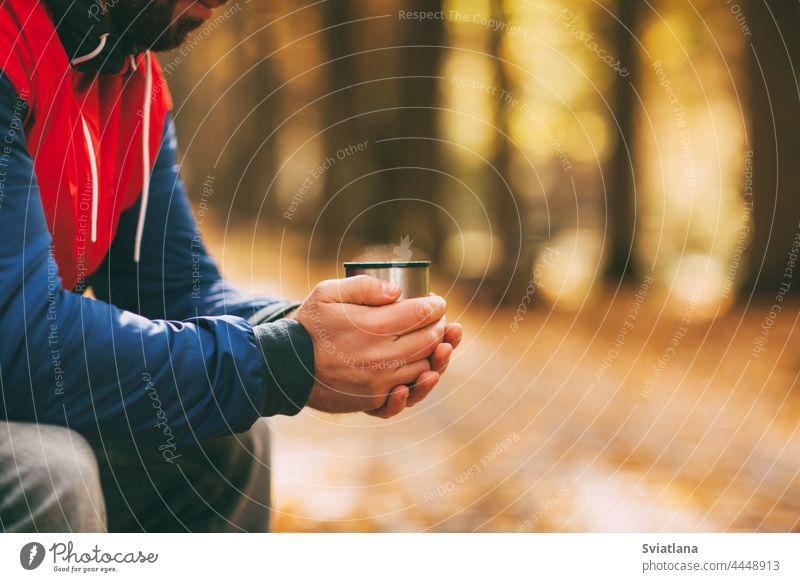 Nahaufnahme der Hände eines Mannes mit einer Tasse Heißgetränk in einem herbstlichen Park oder Wald Tee Bank Herbst Kaffee fallen Reisender Herbstpark im Freien