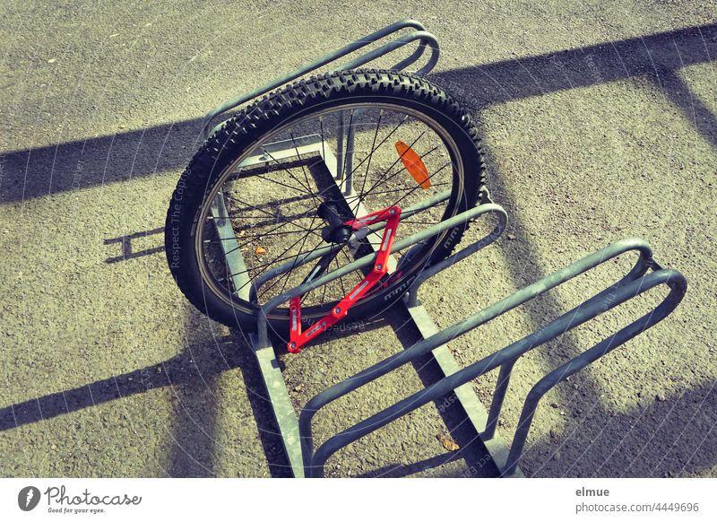 an einen Fahrradständer angeschlossenes Vorderrad eines Fahrrades / Diebstahl / Dreistigkeit Dreistheit dreist Sicherheit Unsicherheit Fahrradschloss