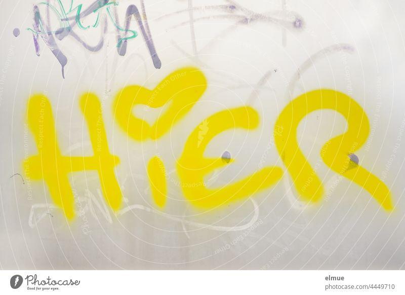 HIER steht in knallig gelben Buchstaben und mit einem Herz als i-Punkt an der grauen Metallwand / Graffito hier Ortsangabe Treffpunkt Graffiti Herzchen Schrift