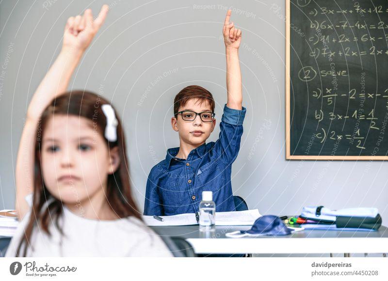Schüler mit Maske auf dem Tisch heben die Hände in der Schule neue Normale Coronavirus Handreichung Klasse teilnehmend Sicherheit Virus Menschen Mädchen Junge