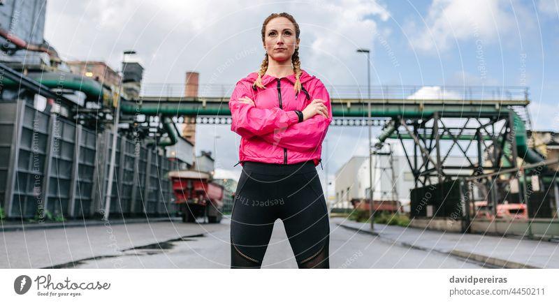 Sportlerin mit verschränkten Armen in Pose vor einer Fabrik verschränkte Arme selbstbewußt geradeaus schauen ernst Läufer Transparente Netz Kopfball Panorama