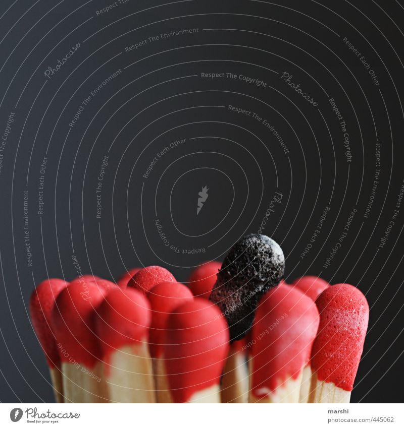 einer ist immer anders Zeichen rot schwarz Streichholz Brand brennen Farbfoto Innenaufnahme Detailaufnahme