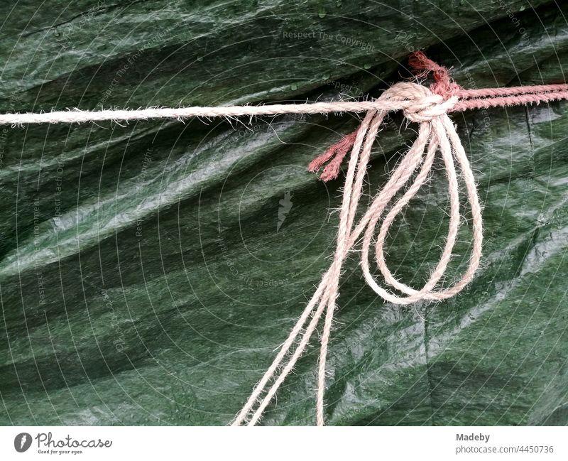 Große grüne Abdeckplane mit klassischer Kordel verzurrt bei Regenwetter im Westend von Frankfurt am Main in Hessen Ebene Plastikplane Kunststoffplane Grün