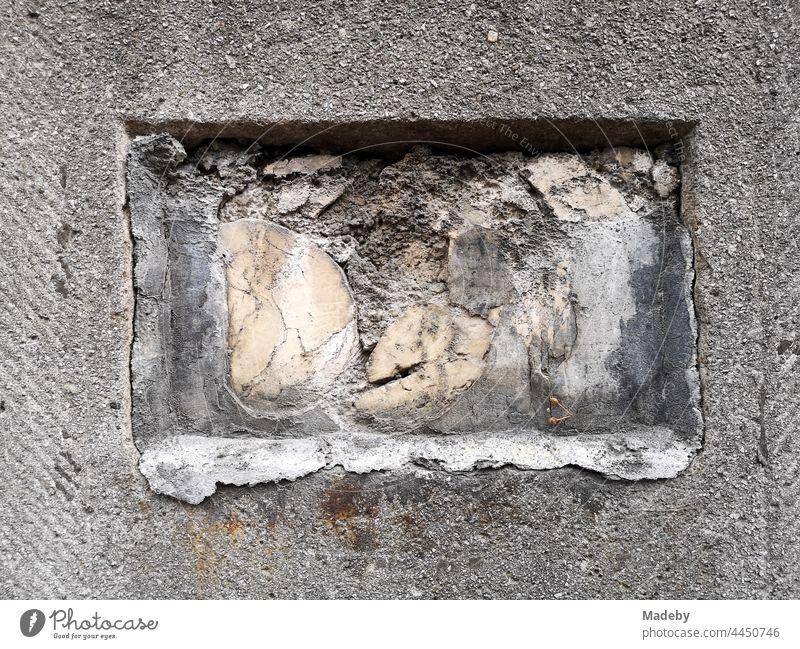 Grauer Steinpfosten mit rechteckiger Öffnung und heuausbröckelndem Gestein am Eingang einer Villa an der Senckenberganlage im Westend von Frankfurt am Main in Hessen
