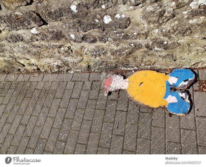 Stilisierte Darstellung eines sitzenden Jungen mit roter Mütze, aufgemalt auf eine Spanplatte, auf dem gepflasterten Gehweg im Sonnenschein in Oerlinghausen bei Bielefeld am Hermannsweg im Teutoburger Wald in Ostwestfalen-Lippe