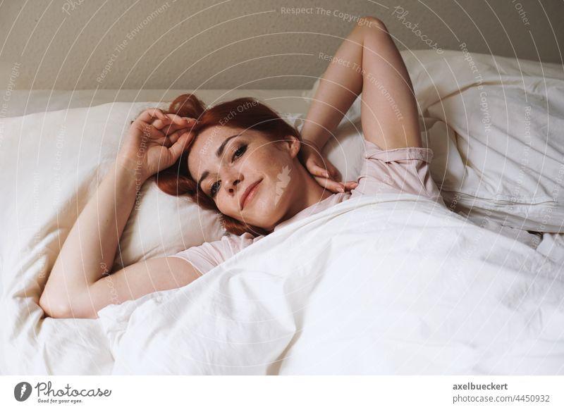 glücklich lächelnde junge Frau, die nach dem Aufwachen im Bett liegt Schlafzimmer Morgen wecken Glück Lächeln heimwärts Erwachsener Person authentisch Lifestyle
