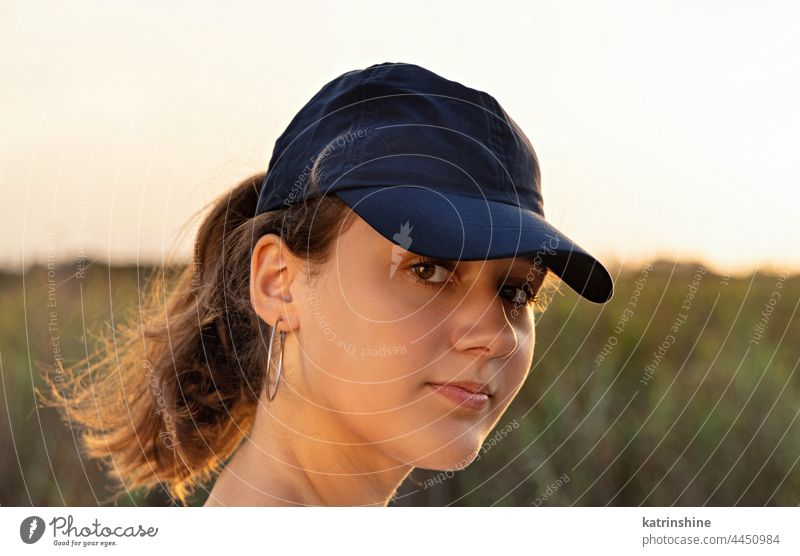Teenager-Mädchen mit dunkelblauer Baseballmütze bei Sonnenuntergang im Freien Jugendlicher Kaukasier Attrappe visier Kopf tragend geradeaus schauend Kindheit