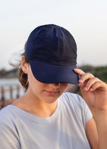 Teenager-Mädchen mit dunkelblauer Baseballmütze und T-Shirt im Freien Jugendlicher Kaukasier Attrappe MEER visier tragend T-Shirts Kindheit Frau Fröhlichkeit