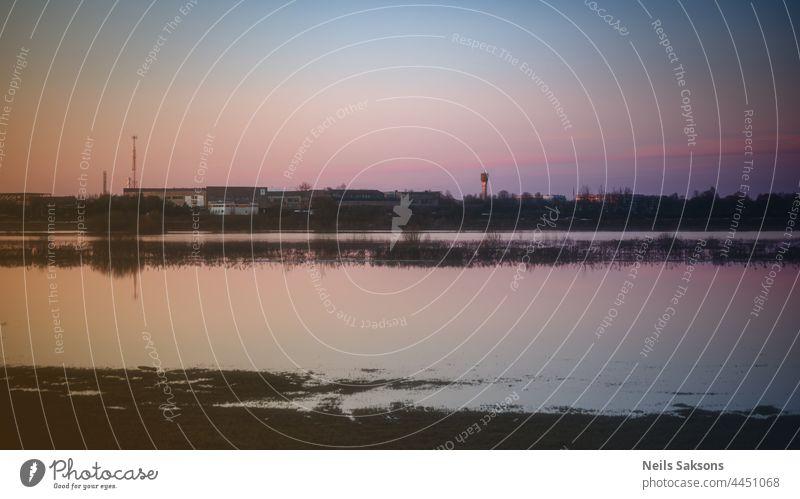 ruhiges, wellenloses Hochwasser auf einer Wiese in Lettland, schöner Frühlingsabend-Sonnenuntergang, klarer Himmel, Fabrik in der Ferne abstrakt Nachmittag
