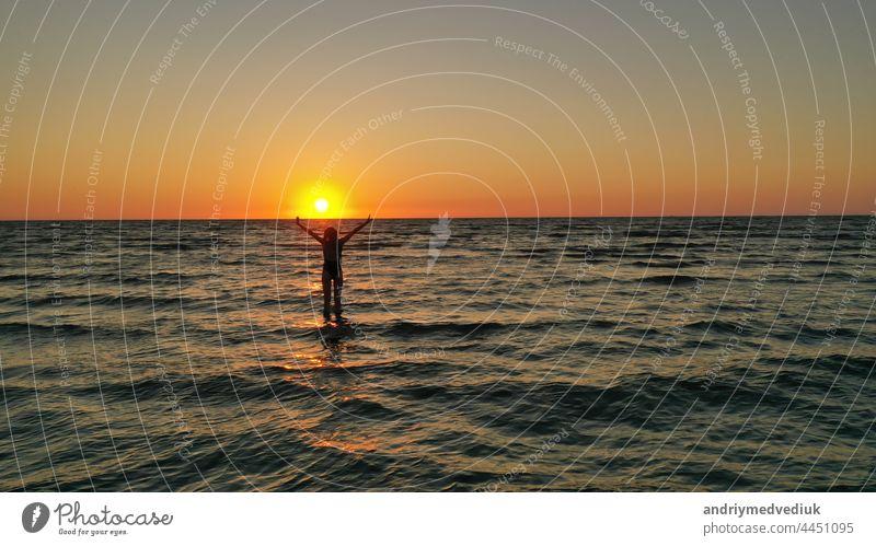 Silhouette eines entspannten jungen Mädchens in einem Badeanzug im Meer bei Sonnenaufgang. Glücklich Urlaub Urlaub Konzept. Frau MEER Strand Sonnenuntergang