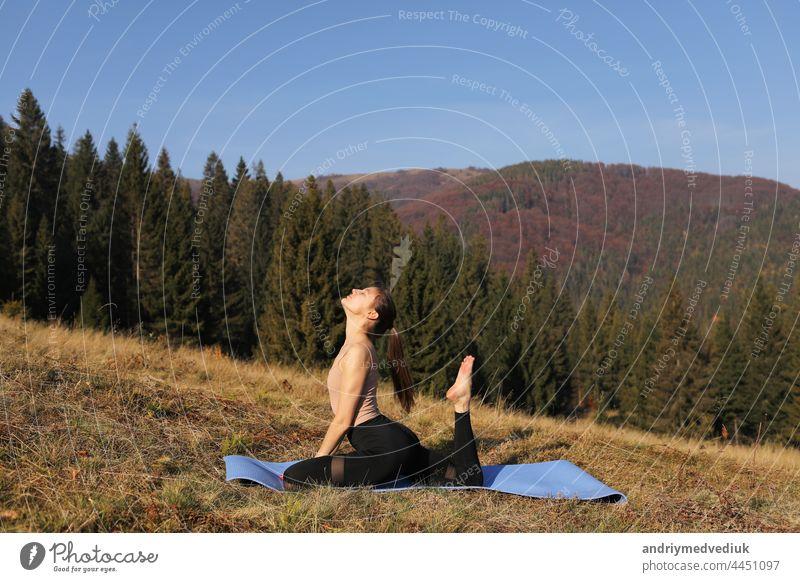Junge fitte Frau macht Übungen auf Yoga-Matte auf dem Hintergrund der sonnigen Berge Hügel. Outdoor-Workout, gesunder Lebensstil. Frau im Sportanzug dehnt sich in der Natur gegen den Wald am Morgen