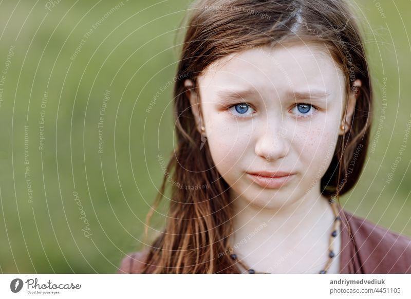Porträt von traurig weinen emotionale niedliche kleine Mädchen Blick auf die Kamera mit Gesicht der tiefen Traurigkeit und Trauer im Freien. Trauriges Kind mit blauen Augen, Kopie Raum