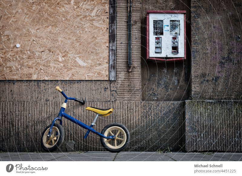 Kinderlaufrad und defekter Kaugummiautomat an einer alten, braunen Hauswand Kinderrad Laufrad Kindheit Kaugummikasten Automat Nostalgie Wand früher Erinnerung