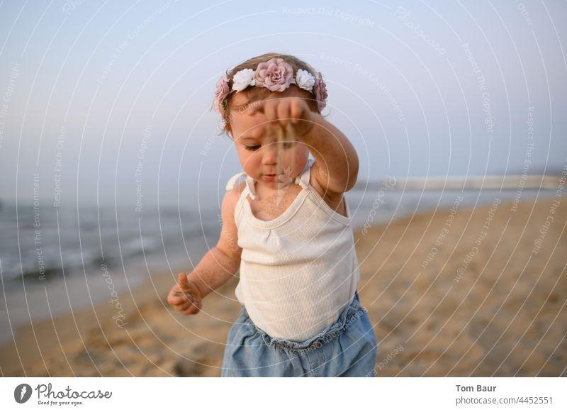 Mädchen mit Blumen in den Haaren spielt am Strand mit Sand - die Zeit rieselt durch die Finger Baby Kleinkind Kind Hand Gesicht 0-12 Monate Auge Blick