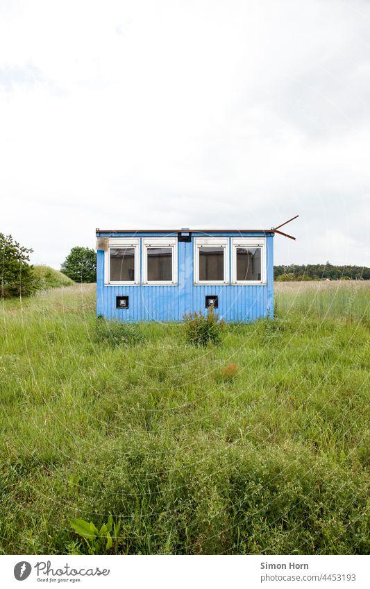 Containerhaus Wiese Unterkunft gestrandet Menschenleer Haus Wohnmobil Fenster provisorisch Flucht Versteck Gras blau Mauer trist Bauwerk