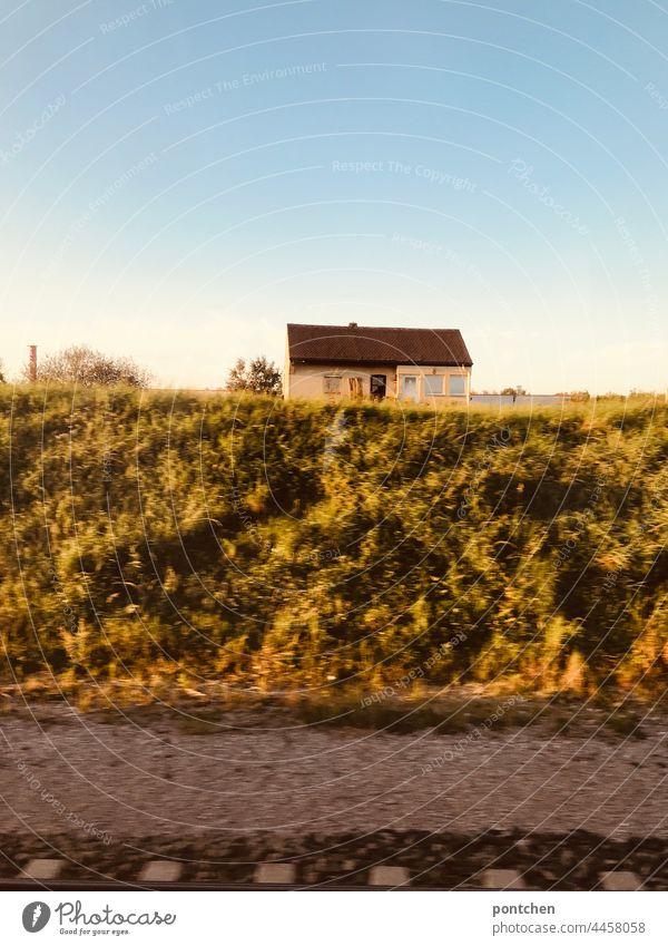 Blick aus dem Zug. Goldener Herbst. Ein kleines altes Haus am Gleiß zugfahrt herbst sonne goldener herbst schiene gleiß landschaft verlassen