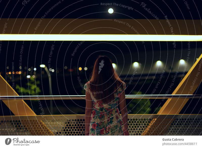 Frau von hinten mit Blick auf die Nacht, die Lichter der Stadt und den Mond. Nachtaufnahme Licht & Schatten Nachthimmel Außenaufnahme dunkel Mondschein