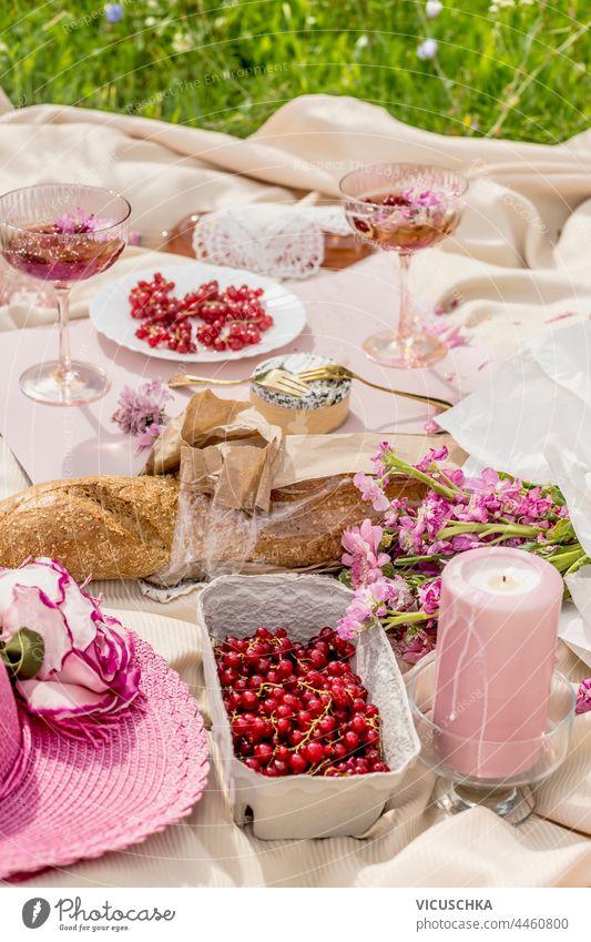 Ästhetisches Picknick mit Baguette, Sektgläsern, Beeren, Käse, Kerzen und rosa Blumenstrauß auf beiger Decke. Draußen Ästhetik Brille Champagne Haufen im Freien
