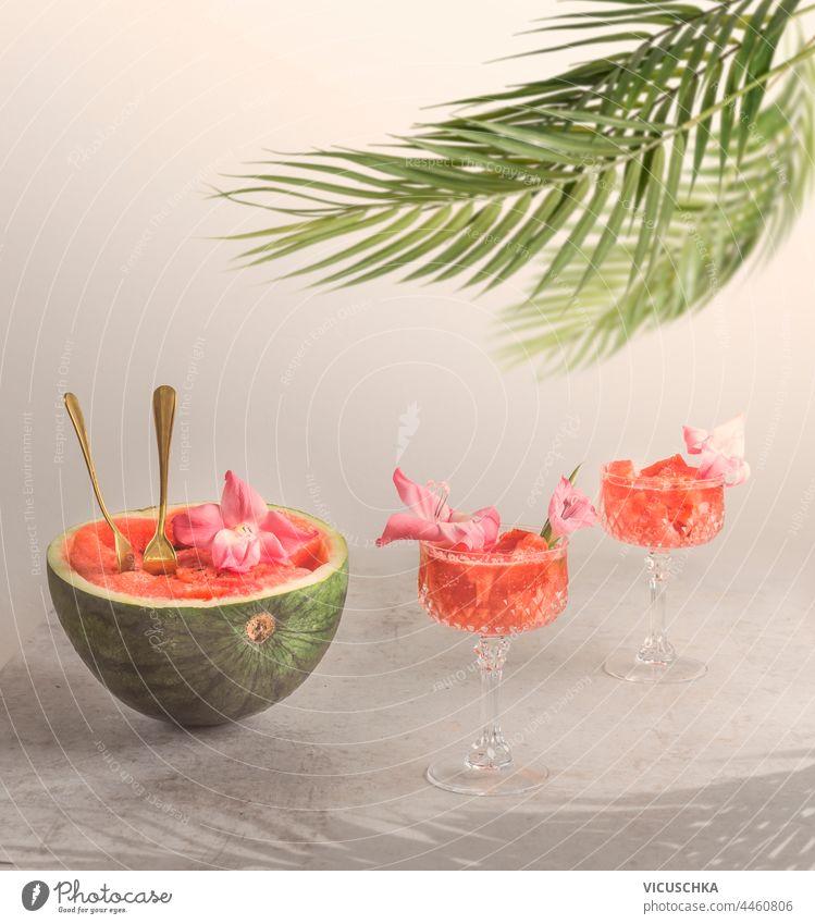 Leckere Wassermelonen-Cocktails in Gläsern mit einer halben Wassermelone, die mit Blumen verziert ist. Sommerliche Erfrischungsgetränke geschmackvoll Brille