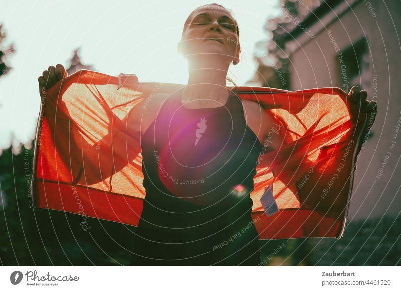 Sportliche Frau breitet nach Training die Arme aus, im Gegenlicht mit roter Jacke sportlich Sonne Flares Silhouette Licht Sonnenlicht Körper Laufen Joggen