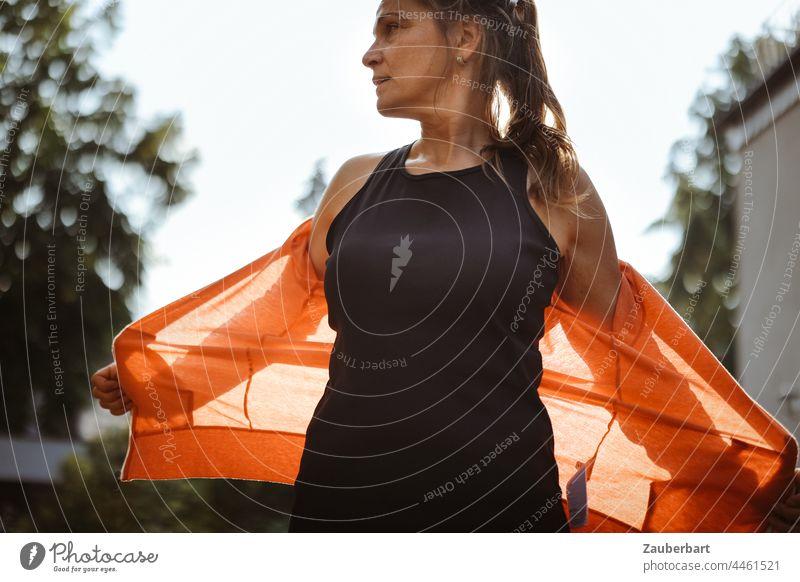 Sportliche Frau breitet nach Training die Arme aus, im Gegenlicht mit roter Jacke und schwarzem Shirt sportlich Sonne Flares Silhouette Licht Sonnenlicht Körper