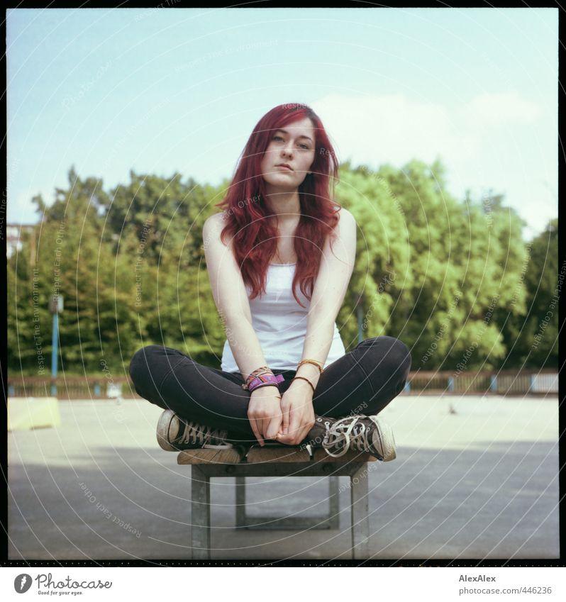 Das Mädchen von der Rollerbahn Jugendliche schön grün rot Junge Frau Erwachsene 18-30 Jahre Holz Park sitzen authentisch Beton beobachten Neugier dünn Jeanshose