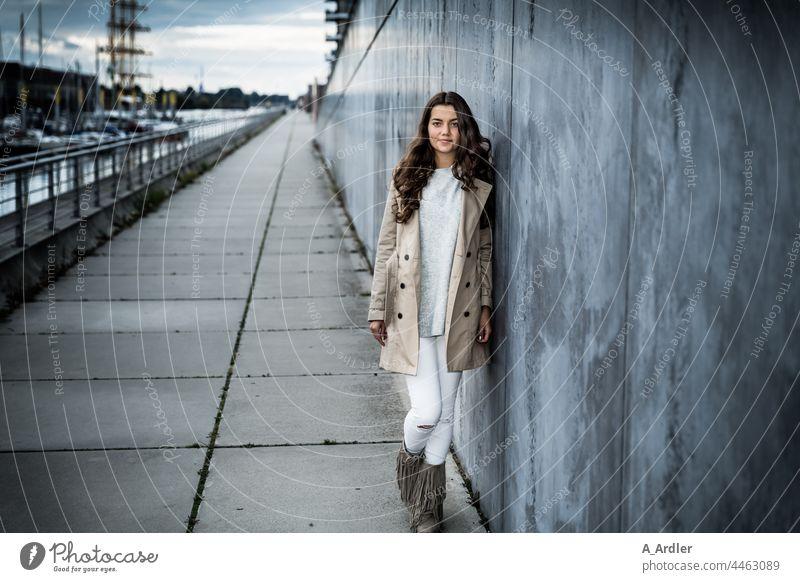 junge Frau im Mantel lehnt an einer Mauer, Hafen im Hintergrund Mädchen Junge Frau Abend abendämmerung Mensch Wand Mode Bekleidung brünett langhaarig