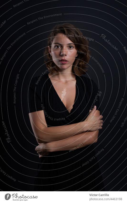 Eine junge schöne Frau, die in einem schwarzen Kleid und mit schwarzem Hintergrund in die Kamera schaut 20-25 Erwachsener attraktiv lässig Nahaufnahme Konzepte