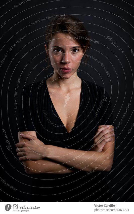 Eine junge schöne Frau, die in einem schwarzen Kleid und mit schwarzem Hintergrund in die Kamera schaut 20-25 Erwachsener attraktiv Schönheit brünett lässig