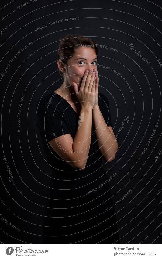Eine junge schöne Frau überrascht von etwas in einem Studio Schuss in schwarzem Kleid und Hintergrund 20-25 Erwachsener attraktiv Schönheit brünett lässig