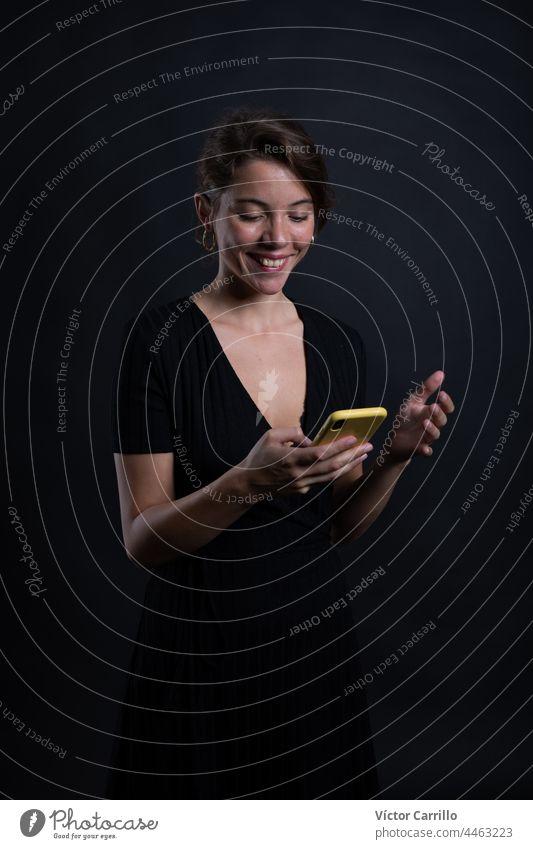 Eine junge schöne Frau mit einem Smartphone in einem Studio Schuss in schwarzem Kleid und Hintergrund 20-25 Erwachsener attraktiv Schönheit brünett lässig