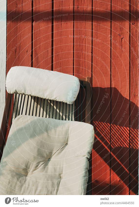 Sitzecke Gartenlaube Wand Holz Bretterwand röt tiefrot Liegestuhl Kissen einfach weich gemütlich Linien