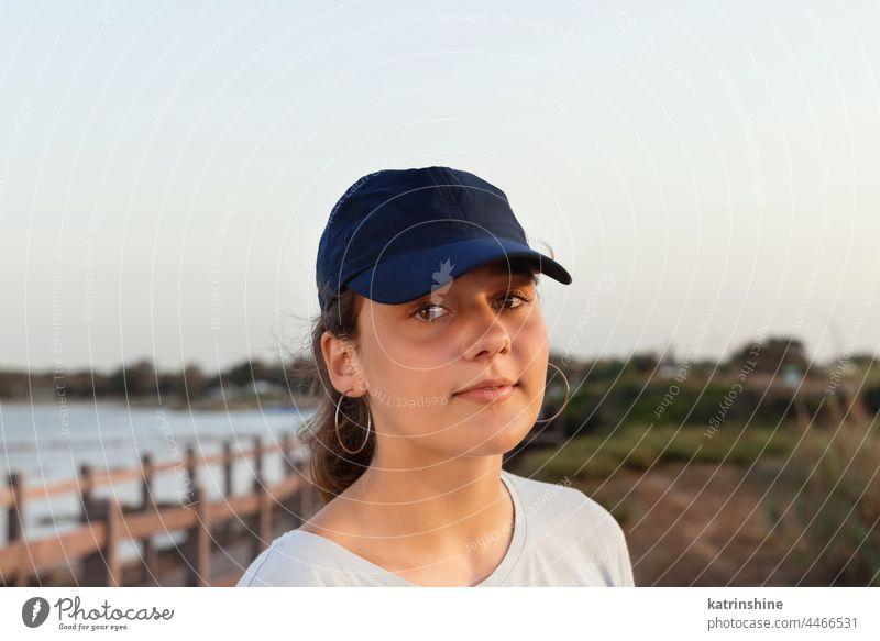Teenager-Mädchen mit dunkelblauer Baseballmütze steht bei Sonnenuntergang am Meer. Kappe Mockup im Freien Jugendlicher Kaukasier Attrappe MEER visier tragend