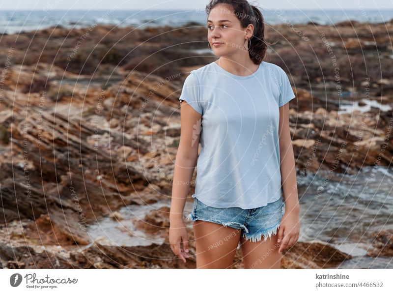 Teenager-Mädchen steht auf Klippe am Meer bei Sonnenuntergang. Shirt Mockup T-Shirt Attrappe blau Kaukasier MEER Felsen Jugendlicher Stein tragend Stehen