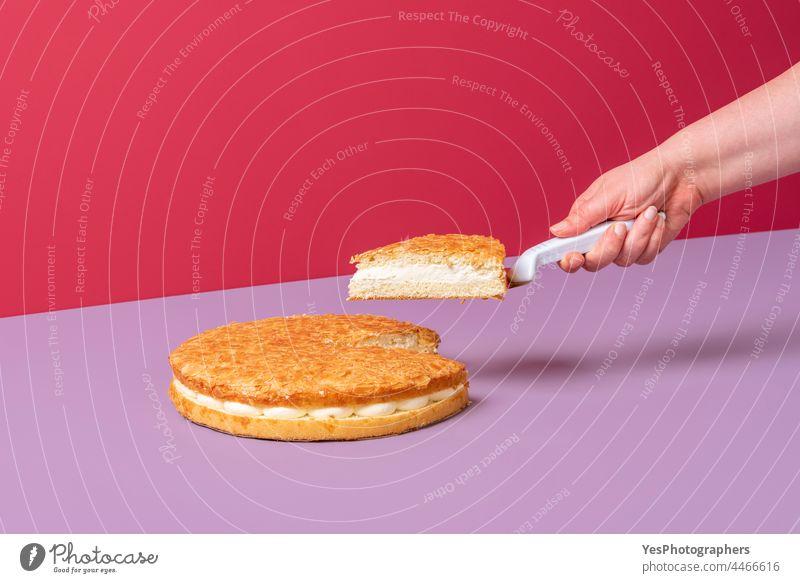 Mandelkuchen minimalistisch auf rosa Hintergrund. Frau nimmt ein Stück Kuchen. Herbst Farbe Sahne cremig Küche geschnitten lecker Dessert Lebensmittel frisch