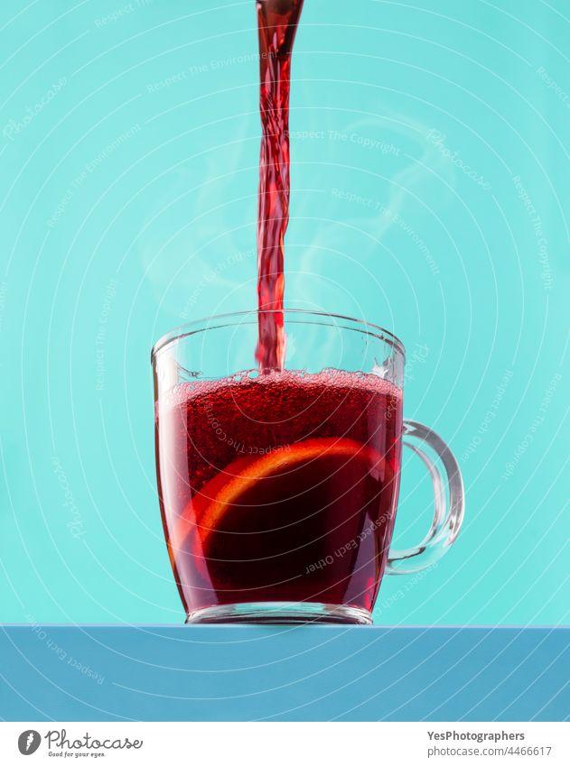 Heißen Glühwein in die Tasse gießen. Heißer Rotwein in einem Glasbecher. Alkohol Winkel Aroma Herbst Hintergrund Getränk blau Feier Weihnachten Nahaufnahme