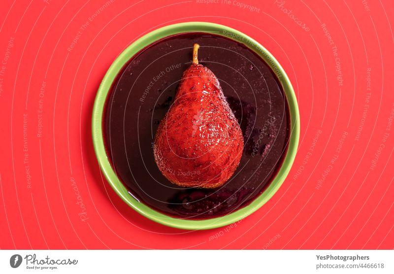 Rotweinpochierte Birne auf dem Teller, Ansicht von oben. Alkohol Herbst Hintergrund gekocht Weihnachten Farbe Küche ausschneiden lecker Dessert Diät