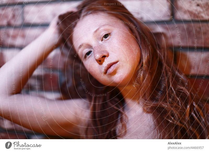 Junge, rothaarige, sommersprossige Frau hält ihre langen Haare nach hinten hoch und schaut seitlich in die Kamera langhaarig sommersprossen Porträt rotblond