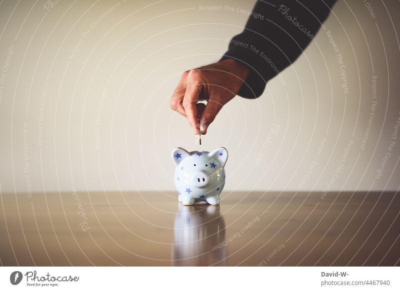 Münze in ein Sparschwein werfen Spardose sparen Geld Euromünzen Hand Mann Geldmünzen Erfolg sparsam Zukunft Zukunftsorientiert