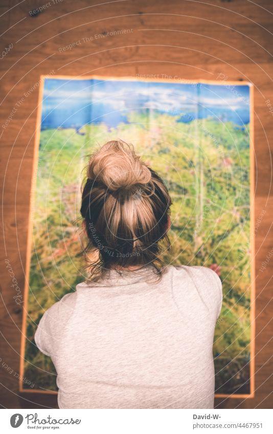 Frau vor einer Landkarte plant den Urlaub. Wohin geht die Reise? Planung reisen Abenteuer Vorfreude Vorbereitung planen ausgebreitet Euphorie reiseziel Ferien