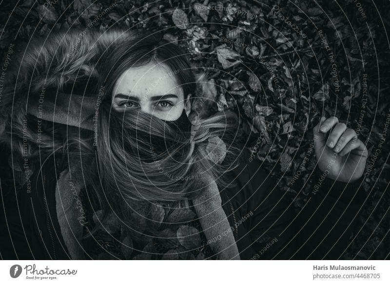 schwarzes und weißes Mädchen mit Gesichtsmaske auf dem Boden liegend allein Herbst Herbstlaub Herbst-Vibes Hintergrund schön schöne Frau Kaukasier Feier