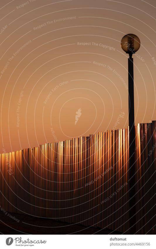 goldenen Sonnenstrahlen Reflexion auf Wellblech mit Laternenpfahl Bauzaun Muster Sonnenuntergang Straßenbeleuchtung Sonnenuntergangsstimmung Blech Blechdach