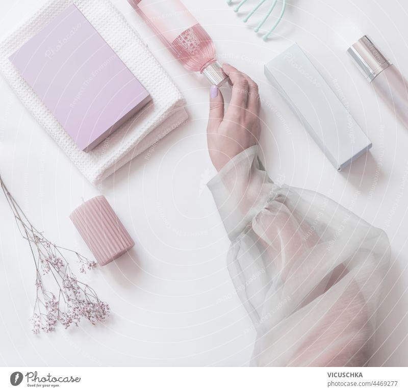 Frauen Hand hält rosa Kosmetik-Flasche auf moderne Schönheit Hintergrund mit Verpackungs-Boxen, Kerzen und Blumen. Ansicht von oben. Pastell gedämpfte Farbe