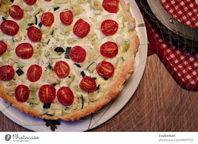 Gemüsequiche mit Kirschtomaten, Zucchini und Lauch auf Teller, karierter Topflappen Quiche Gemüsekuchen Tomaten rot Lebensmittel rund Holztisch backen Mahlzeit