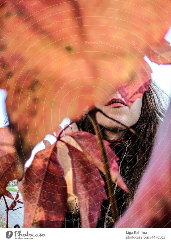 Lippen versteckt zwischen Herbstblättern Mund Frau Gesicht Auge schön Lippenstift Erwachsene Schminke feminin Mensch obskur verborgen Farbfoto herbstlich