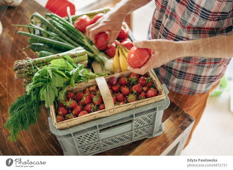 Mann beim Auspacken seiner Einkäufe in der Küche zu Hause Hand Menschen Person Auspacken von Lebensmitteln Ackerbau Spargel Korb Kasten kaufen Essen zubereiten