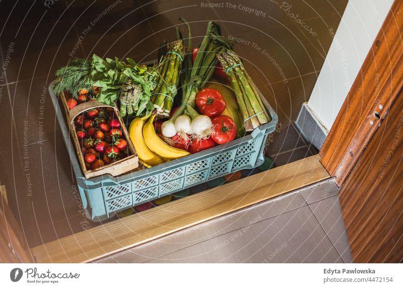 Obst- und Gemüselieferkasten vor einer Wohnungstür Spargel Korb Kasten kaufen Essen zubereiten Coronavirus Kurier lecker Versand Lieferbox Diät Tür Lebensmittel